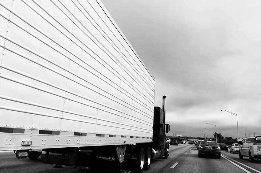 enclosed truck on highway black and white