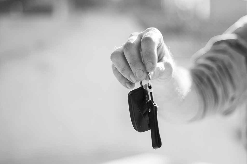 dealership handing keys to customer black and white