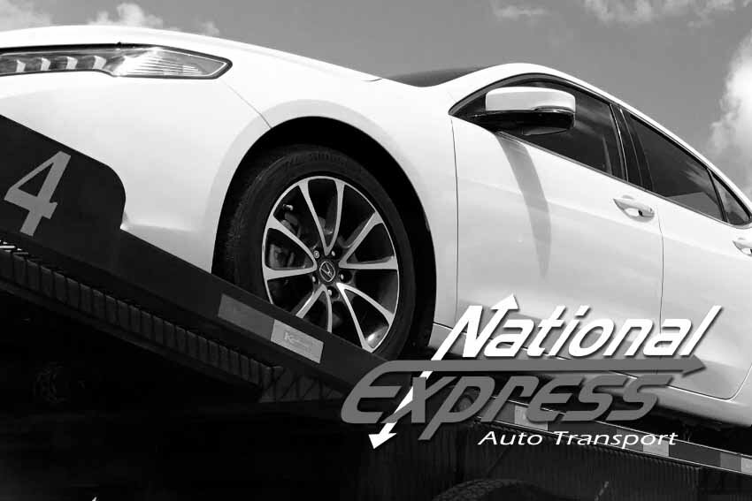 car on top of auto transporter black and white image